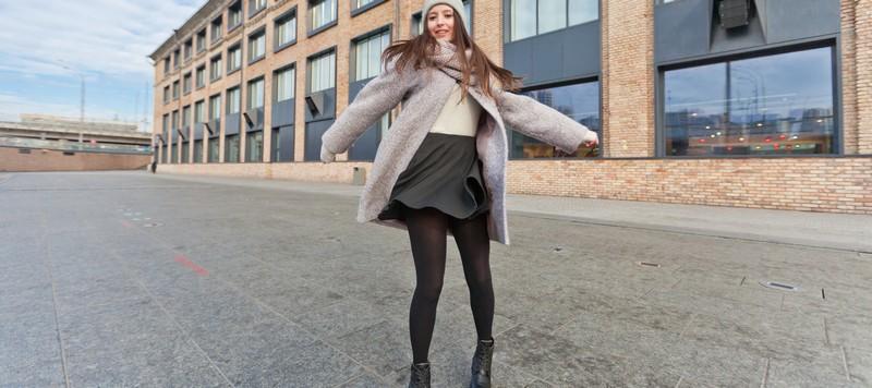 Девушка в черной юбке на фоне здания осень